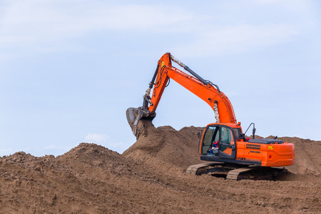 Earthworks construction heavy excavator machine moving sand closeup photo.