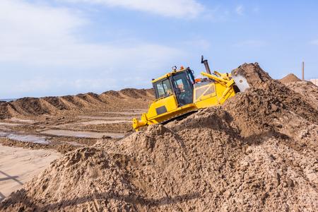 Earthworks construction heavy dozer industrial machine pushing sand closeup photo.