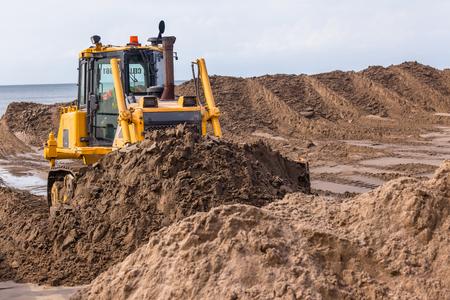 Earthworks construction industrial heavy dozer machine pushing sand closeup photo.