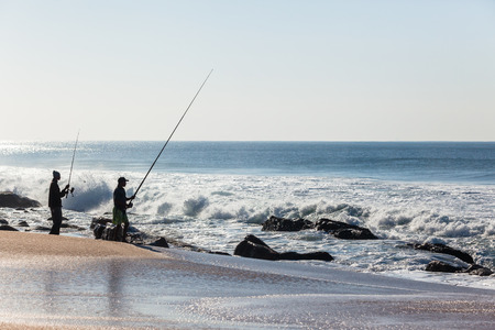 Fishing beach coastline along ocean waves with distant unidentified silhouetted fishermen.