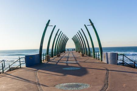 Ocean pier public jetty with elephant tusk design structures at Umhlanga beach facing blue sky water horizon. Banco de Imagens