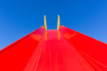 Playground closeup inside childrens red painted slide chute looking upwards towards blue sky. Stock Photo