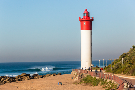 Beach Lighthouse red white structure closeup with blue ocean horizon waves a holiday lifestyle landscape.