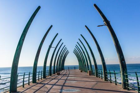 Beach ocean pier jetty with structure designed elephant tusks morning blue sky horizon landscape. Banco de Imagens
