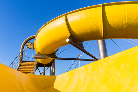Amusement park swimming pool yellow water slide structure closeup family holiday destination.