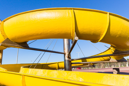 Swimming pool yellow water slide structure closeup family holiday destination.