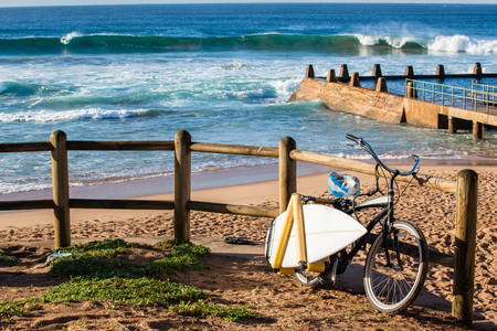 Gone Surfing Surfers spare surfboard on bicycle racks at beach front of ocean waves pool landscape.