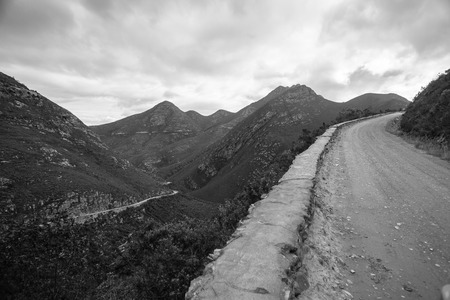 High rugged old dirt road pass through rugged mountains in black and white landscape.