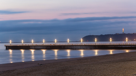 Beach ocean pedestrian pier jetty lights reflections at dawn morning lights Durban harbor port entry beachfront.