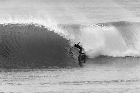 Surfing surfer riding motion on hollow curling wave in danger of wipeout in black and white photo contrasts. Imagens