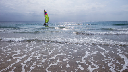 Yacht small twin hull racing sporting boat launches off beach shallows towards ocean horizon.
