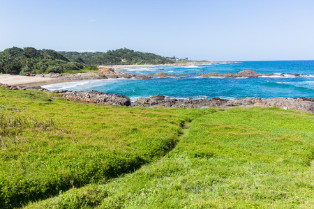 Beach coves with blue ocean wave waters to horizon with rocky coastline and green vegetation landscape