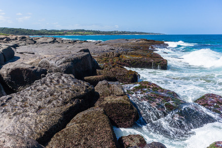 Beach large rocky boulders front of  blue ocean wave waters to horizon along coastline  landscape