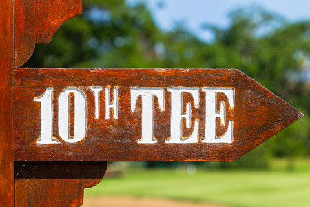 Golf course sign directions to 10th tee box front of last hole green and  trees on scenic coastal course. Reklamní fotografie