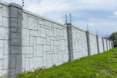 Boundary eight foot wall fence structure gray design concrete decor with electrical shock wires.