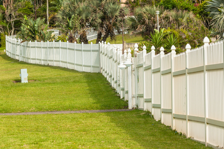 White boundary vertical slat plastic pvc fence along roadside grass landscape. Stock Photo