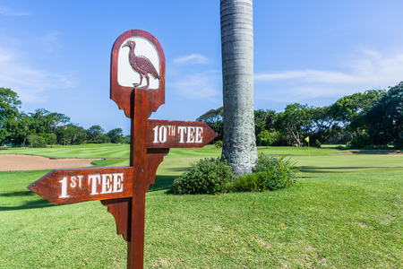 Golf course sign directions to 1st and 10th tee boxs front of last hole green and  trees on scenic coastal course. Stock Photo