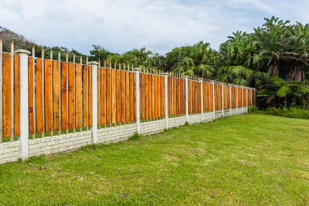 Boundary wall fence contructed with concrete vertical columns steel and wood slats with palm trees.