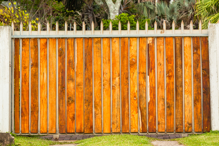 Boundary vehicle gate fence contructed with concrete vertical columns steel and wood slats with palm trees. Stock Photo