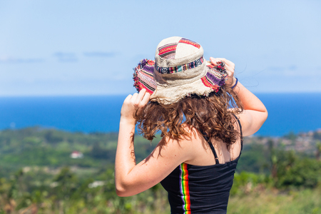 Young teen girl woman on holiday closeup behind back shoulders hands holding hat from hilltop winds looking over the distant blue ocean and green summer countryside coastline.