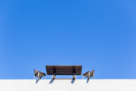 Table Chairs blue sky upward view on edge of building top floor outdoors for a business people meeting concept on close to crashing falling to destruction .