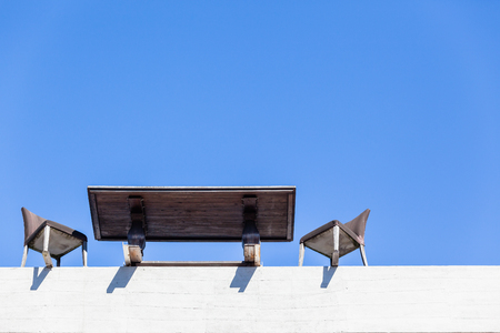 Table Chairs blue sky upward view on edge building top floor outdoors for a business people meeting concept on close to crashing falling to destruction .