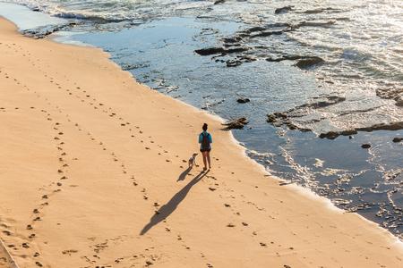 Donna e cane che camminano sulla spiaggia rocciosa dell'oceano acqua litorale la mattina presto esercizio foto aerea. Archivio Fotografico