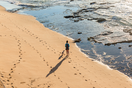 Woman and dog walking beach rocky ocean water shoreline early morning exercise overhead photo.