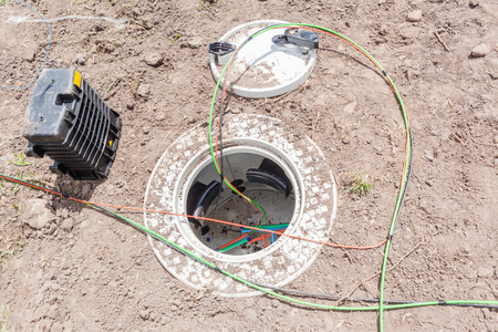 Communications construction of new internet fast speed fiber optic cables been installed underground by technicians in connection water proof cases and inserted box along road of residential homes .