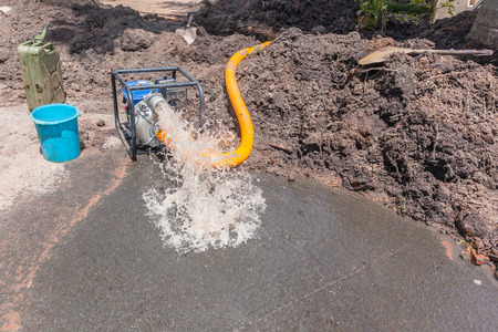 Plumbing pumping water from earthwork trench digging repairs of broken main pipe in residential road area with mobile portable motor pump draining damage.