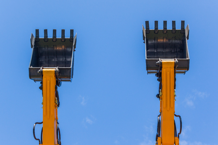 Construction business industry two new excavators earth mover machines together outdoors with steel arms extended and bucket scoops closeup into blue sky.