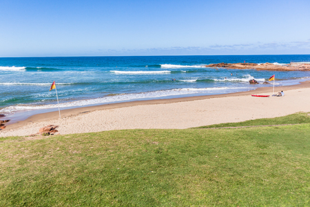 Scenic beach blue water ocean lifeguard flags at Scottborough a surfers surfing fishing sporting holiday landscape.
