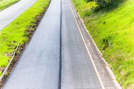 Road highway dual lanes with one lane resurfaced with new asphalt tar for vehicle safety improvement. Stock Photo