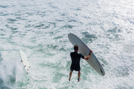 Surferswith surfboards jump off beach pier jetty into ocean water for quick entry to go surfing  waves closeup behind action photo. Stock Photo