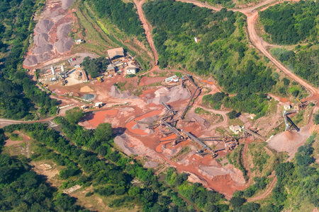Large open cast stone quarry iwith industrial  trucks conveyors crushing machines in rural countryside valley a flying aerial overhead photo of landscape 版權商用圖片