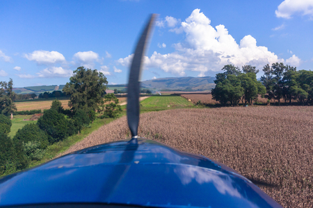 Pilots cockpit landing approach view in light propeller aircraft plane in rural farming countryside over maize crops onto grass runway/