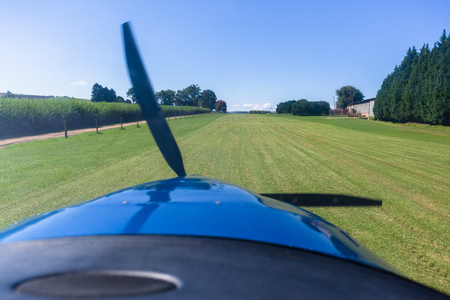 Pilots cockpit takeoff fllight view in light propellrr aircraft plane in rural farming countryside grass runway. Stock Photo