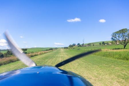 Pilots cockpit landing approach view in light propeller aircraft plane in rural farming countryside grass runway/