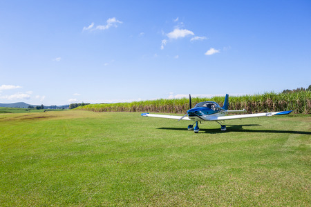 Light single prop aircraft plane parked on rural countryside farm grass airstrip runway between agriculture crops.