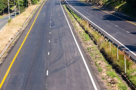 Road highway new section of asphalt tar white  painted lines on two lanes middle overhead photo detail.