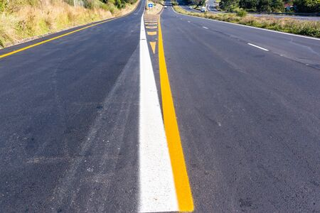 Road highway new asphalt tarmac painted white yellow exit markings directions lines closeup middle overhead photo detail.