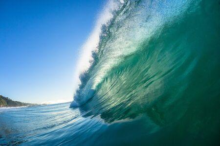 Ocean swimming closeup inside hollow crashing wave water towards camera lens.