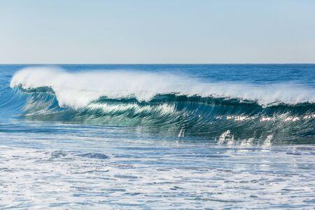 Ocean blues waves crashing beaking on shallow sandbars. 写真素材