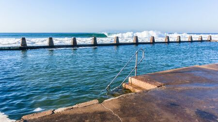 Beach tidal swimming pool with ocean waves breaking crashing on shallow reefs