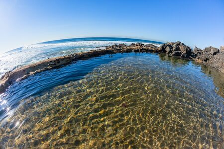 Small beach rocky tidal swimming pool front of blue ocean waves scenic horizon landscape. Stock Photo