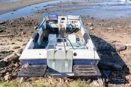 Abandoned small ski fishing boat on harbor rocky sand shoreline damaged destroyed vessel.