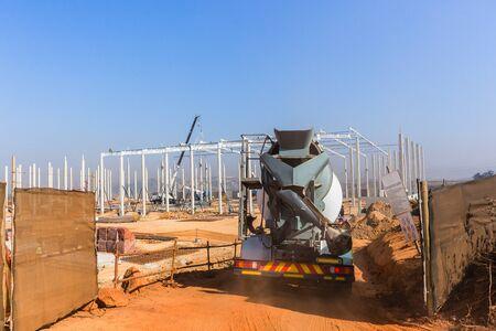 Industriebau-Zementbeton-LKW betritt das Gelände der neuen Lagerhalle, die mit Betonsäulen und Stahldachträgern errichtet wurde. Standard-Bild