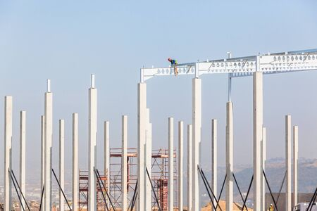 Industrial construction on site of new warehouse worker on top of high erected concrete columns and steel roof beams. Фото со стока