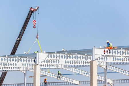 Industrial construction on site of new warehouse workers on top of high erected concrete columns and steel roof beams.