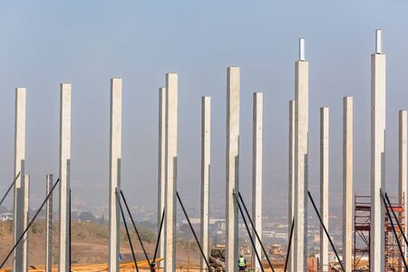 Industrial construction on site of new warehouse factory buildings been erected with concrete columns and steel roof beams.